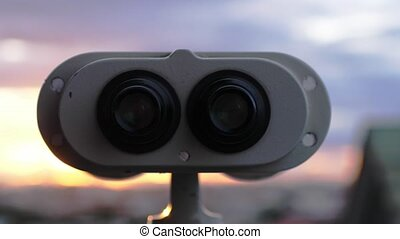 Binoculars lookout at the city during amazing sunset in slow...