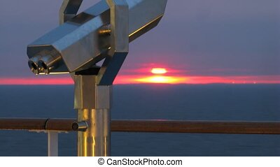 Binoculars on cruise liner in front of sunshine, time lapse
