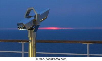 Binoculars on cruise liner in front of sunset, time lapse
