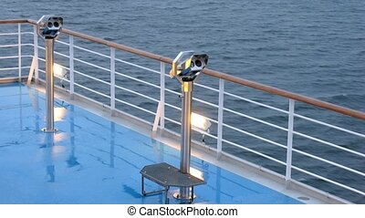 Binoculars on deck of cruise liner in evening time, time lapse