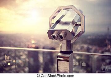 Binoculars or telescope on top of scyscraper at observation...