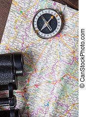 Binoculars with compass on map.