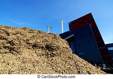 bio power plant with storage of wooden fuel against blue sky