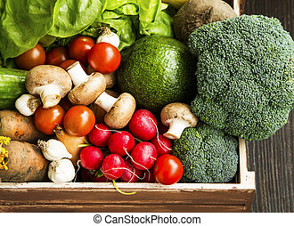 Bio vegetables in wooden crate with radish, salad, mushrooms, broccoli, tomatoes