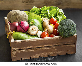 Bio vegetables with radish, salad, mushrooms, broccoli, tomatoes in wooden crate