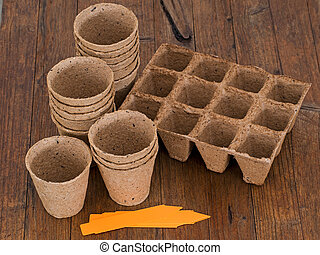 Biodegradable peat pots for sowing seeds - On wooden bench. ...