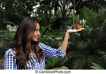 biodiversity: butterfly sitting on the hand of a young woman in the forest