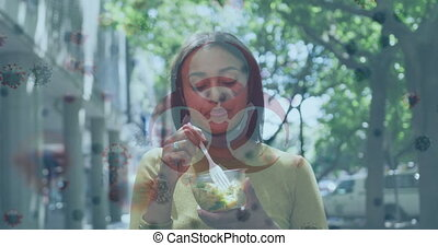 Biohazard symbol against african american woman with lowered face mask having a snack outdoors. coronavirus covid 19 pandemic concept