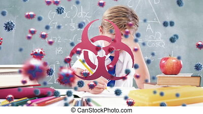 Animation of Covid 19 coronavirus cells spreading with biohazard symbols over schoolboy writing in school class. Education back to school coronavirus pandemic concept digitally generated image.