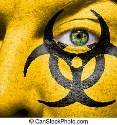 Biohazard symbol painted on face with green eye to raise...