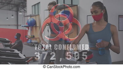 Biohazard symbol with with increasing cases against woman cleaning stationary bike with disinfectant. coronavirus covid-19 pandemic and fitness concept