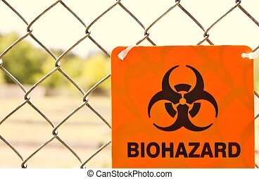 Biohazard sign attached to a chain link fence.