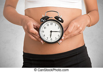Concept of biological clock. Woman holding clock in front of her belly, isolated in white