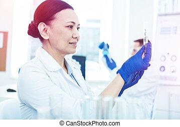Smart intelligent woman holding a test sample
