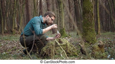 Biologist taking part of green moss for studying - Confident...