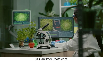 Biologist woman examining biological slide for medical expertise using microscope. Chemist scientist analyzing organic agriculture plants in microbiology scientific laboratory