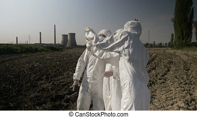 Biologists workers in hazmat clothing looking at...