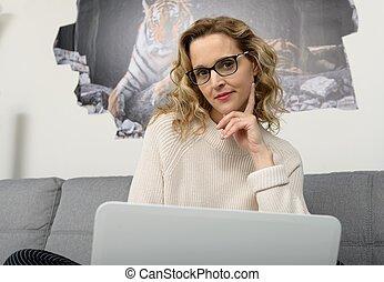 biondo, donna, usando, sofà, con, laptop