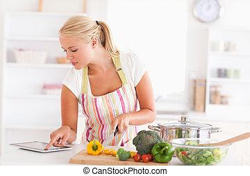 biondo, donna, usando, uno, tavoletta, computer, cucinare