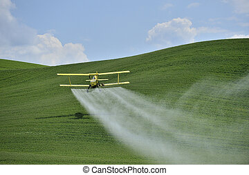 Biplane Crop Duster spraying a farm field. - Agriculture: a...