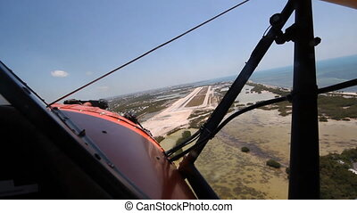 Shot from front cockpit of antique 1940 UPF-7 Waco biplane approaching runway. 1 of 2 shots. Key West, Florida.