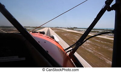 Shot from front cockpit of antique 1940 UPF-7 Waco biplane approaching runway. 2 of 2 shots. Key West, Florida.