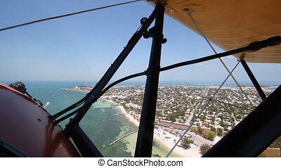 Shot from front cockpit of antique 1940 UPF-7 Waco biplane. Flying over Key West, Florida.