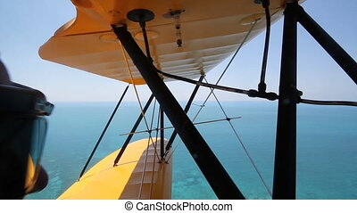 Shot from front cockpit of antique 1940 UPF-7 Waco biplane. Passenger with goggles at left of frame. Flying over ocean off Key West in Florida.