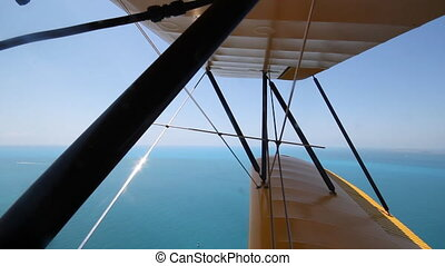 Biplane over ocean. Two shots. - Shot from front cockpit of...