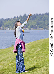 Biracial asian girl flying kite by the lake