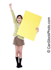 Biracial asian girl in green sweater holidng blank yellow sign, arm cheering in air