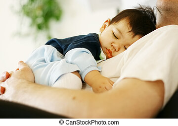 Biracial baby boy asleep on father's chest