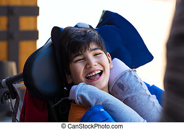 Biracial eleven year old boy in wheelchair outdoors, smiling