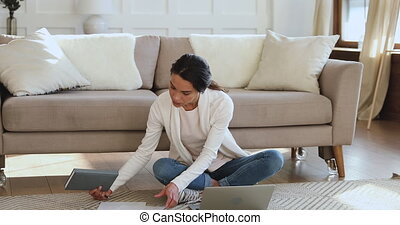 Biracial female student sitting on floor, doing homework.