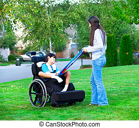 Biracial older sister playing outdoors with disabled little ...