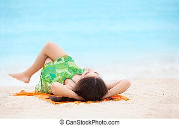 Biracial teen girl arms lying on beach relaxing by ocean water