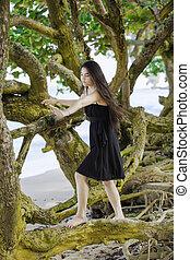 Biracial teen girl climbing on sprawling branches at Hawaiian beach