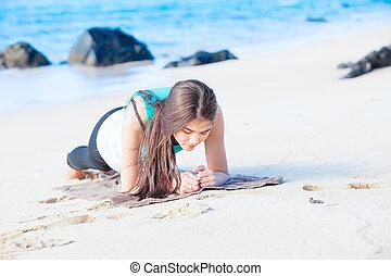 Biracial teen girl exercising on tropical beach, planking