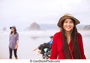 Biracial teen girl in red dress and hat at beach