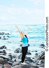 Biracial teen girl on rocks by ocean praising God