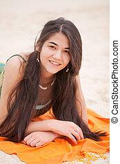 Biracial yeen girl lying on orange blanket at beach