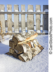 Birch firewood in the snow against a wooden fence