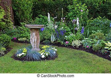 Bird bath by flower bed. - Bird bath in a beautiful summer ...