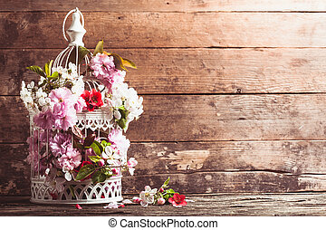 Bird cage with spring blossom of sakura and fruit flowers. Wedding decorations with copy space