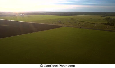 bird eye flight over pictorial landscape with fields at sunset