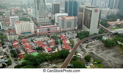 Bird eye time lapse view of railways across road against city landscape. Kuala Lumpur, Malaysia