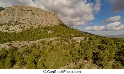 Bird-eye view at the ruins of ancient temple with mountains on the background. Priene, Turkey. Aerial, 4k.