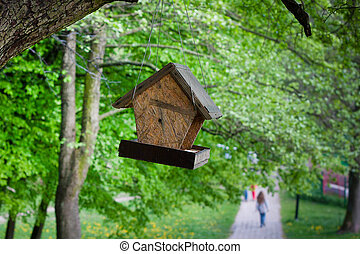 Bird feeder from chipboard hanging on a tree in the park.