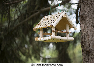 Bird feeders made in form of house and Titmouse eating feed, autumn outdoor