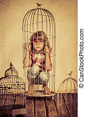 Bird in cage - Sad child in steel cage. Human rights concept
